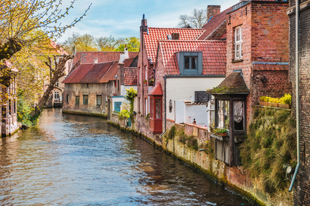 Old houses along beautiful canals in spring in Bruges, Belgium