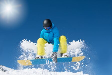 Active snowboarder jumping in winter mountains Foto de archivo