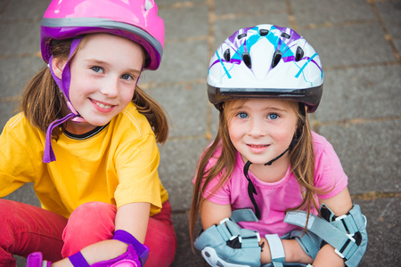 inline skater: Two smiling kids in protective helmet and sportswear for cycling