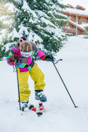 Kid at a winter resort putting on skis