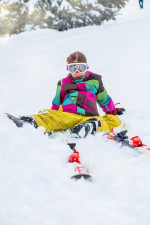 Happy kid in ski goggles sitting in snow photo