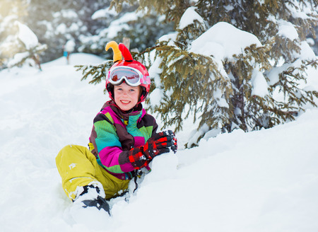Happy kid with helmet on sitting and playing with snow  photo
