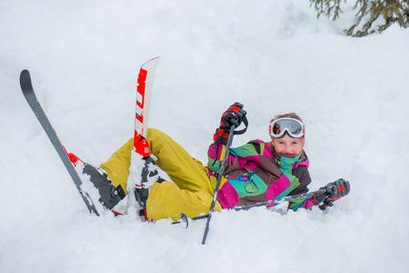 Happy kid lying with skis  in snow Foto de archivo