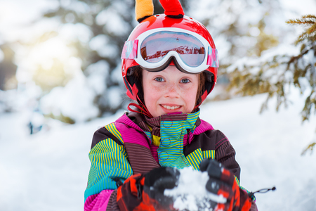 Young active skier in sport helmet playing with snow photo