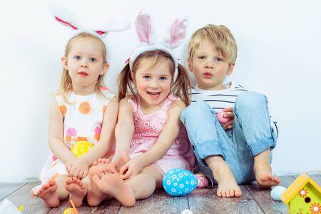 Three smiling preschoolers with Easter bunny ears on Foto de archivo