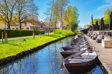 Boats in spring in Giethoorn, a small village in Overijssel province in the Netherlands. Part of the village has no car roads and some houses are accessible by boat only. Stock Photo
