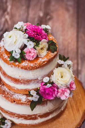 Closup shot of a two layered homemade naked cake  decorated with flowers on wooden cut stand