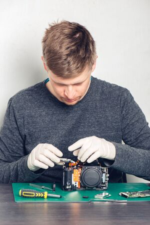 Technician in latex gloves repairing digital camera in a service laboratory