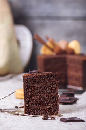 Slice of a chocolate four layered cake shot closeup