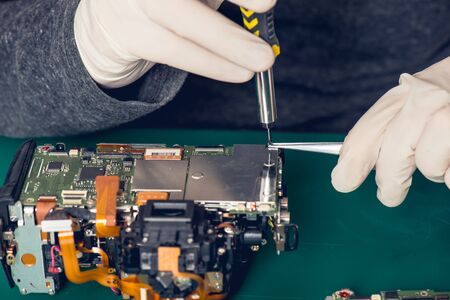 Close up hands of a technician repairing digital camera