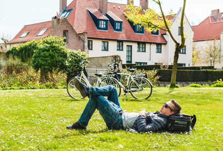 Tourist enjoying spring sunny day on green grass in a park
