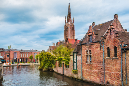Houses along beautiful canals in spring in Bruges; Belgium. In the background there is the church tower of the famous Onze-Lieve-Vrouwekerk Foto de archivo
