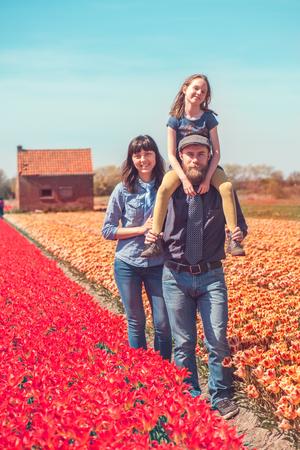 Happy loving family with a kid in a Dutch tulips field  Foto de archivo