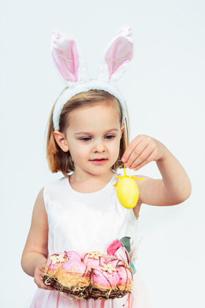 Portrait of a smiling Easter kid holding egg wreath and looking at a yellow egg decoration Foto de archivo
