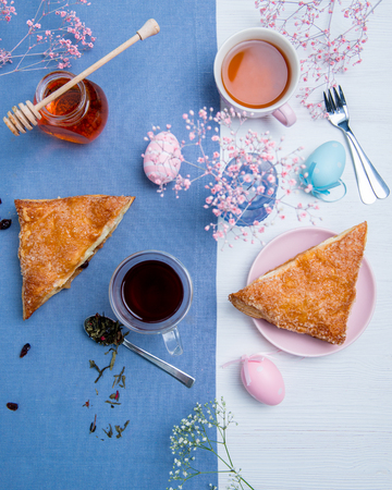 Apple turnovers served with tea along with pink Easter eggs decoration