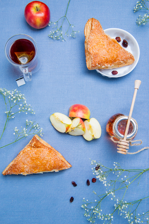 Apple turnovers served on the table covered with blue cloth