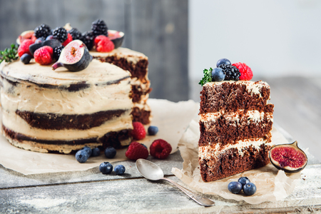 Rustic chocolate cake with buttercream frosting and decorated with berries