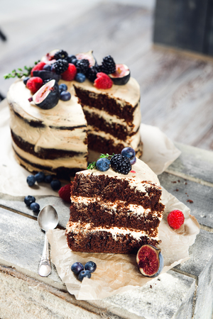 Rustic chocolate cake with one piece cut, lying on parchment paper Foto de archivo