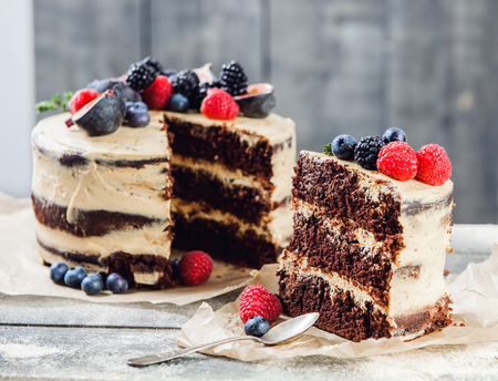Rustic chocolate cake with buttercream frosting and decorated with berries and figs Foto de archivo