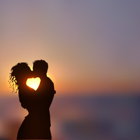 honeymoon suite: Summer poster with a kissing couple silhouette against contrast blue and yellow sunset seascape blurred background.