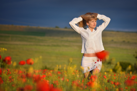 Young beautiful woman with long blond hair in poppy field. Blonde with long hair in white dress on background of red poppy field