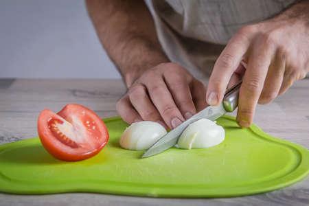 cutting eggs on green cutting board Stock Photo