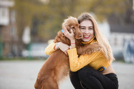 Portrait. Beautiful sexy girl, blonde, young woman, similar to Jennifer Aniston siting with a dog cocker spaniel, hugs, touches, cares. Against the background of city houses. Stock Photo