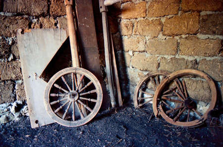 weathered: Old wooden wheels, broken and abandoned. They lie in a stable, dirty and dusty.