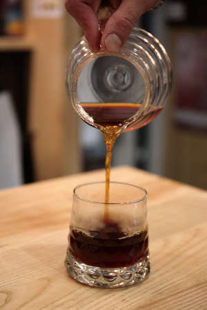 Barista pours a coffin into the glass cup. He serves a drink. Kemex