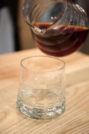 Barista nalewa trumnę do szklanej filiżanki. Podaje drinka.