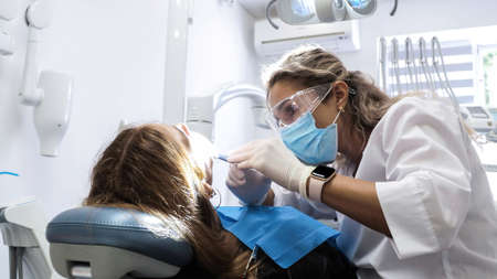 Young woman dentist. Reception at the orthodontist. Replacement of braces. Polishing. Gel bonding. 版權商用圖片