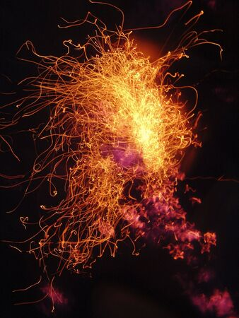 embers: An explosion of fire and embers cascading through the dark like fireworks. Stock Photo