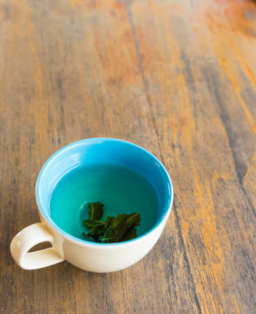 green leaf: Cup of hot green tea  on wood table Stock Photo