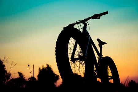 silueta de bicicleta de montaña en la puesta del sol hermosa, fatbike silueta Foto de archivo