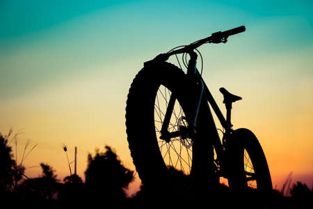 silueta ciclista: silueta de bicicleta de montaña en la puesta del sol hermosa, fatbike silueta Foto de archivo