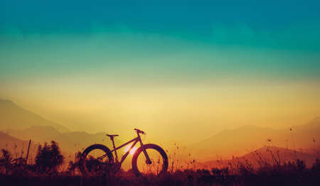 Golden sky sunset and mountain bike silhouette, silhouette fat bike, Silhouette Bicycle  on mountain background
