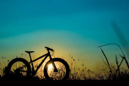 beautiful sunset sky and mountain bike silhouette , silhouette fat bike