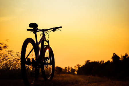 single track: Silhouette of mountain biker in single track on sunset sky