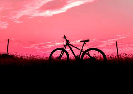 Silhouette Mountain biking, down hill at sunset