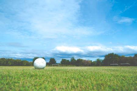 ballsport: Old football on green grass in Stadium on blue sky, Old soccer ball, soccer field Stock Photo