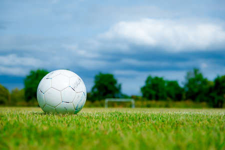 ballsport: Old football on green grass in Stadium on blue sky, Old soccer ball, soccer field Stock Photo