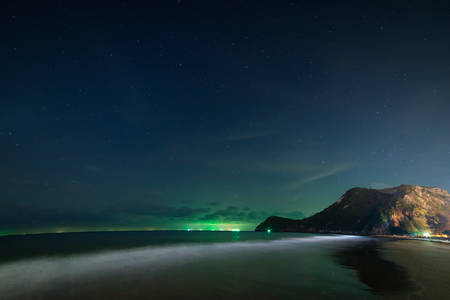 beach and mountains at night sky