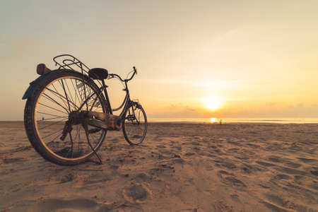 Vintage Bicycle on the beach at sunset Banque d'images