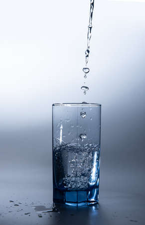 pouring fresh drink water to blue glass Banque d'images