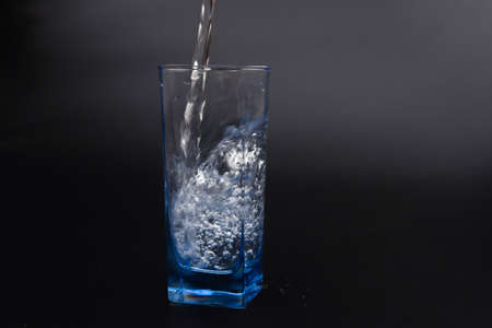 pouring fresh drink water to blue glass on black background Banque d'images