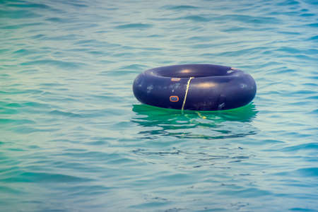 floating ring or  swim tube on blue water swimpool with waves reflecting in the summer sun