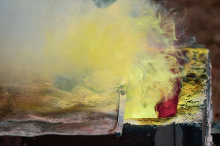 Smoke Molten Gold being poured into Buddha statue in Thailand. Reklamní fotografie