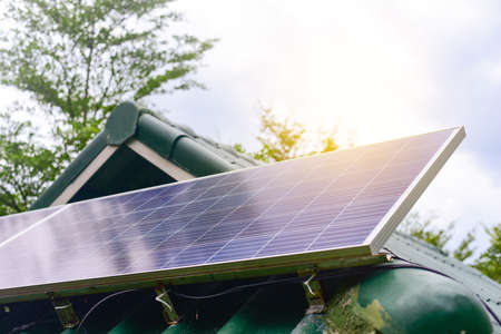 Solar cell in solar farm with green tree and sun lighting reflect, Alternative energy and sustainable energy, photovoltaic, Pure energy Concept.  写真素材
