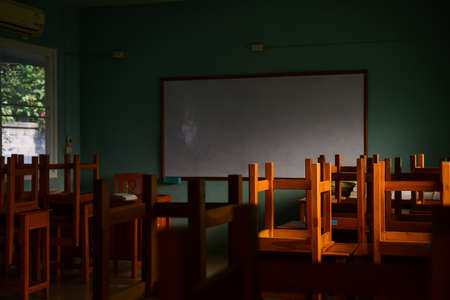 Wooden Chair in the classroom with sunlight.