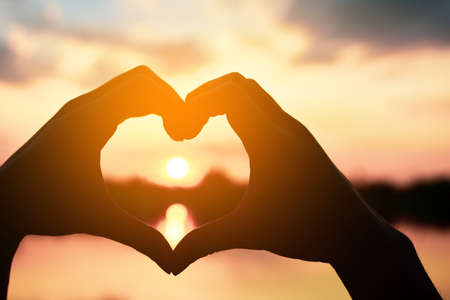 Beautiful Silhouette hand made heart shape on the sunset background.
